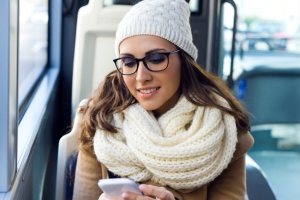 Young beautiful woman using her mobile phone on a  bus.